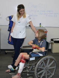 Smiling Rad Tech student and smiling patient in a wheelchair during a mass causality drill