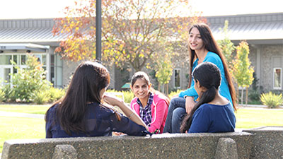 Four students conversing on bench outside Yuba College Library